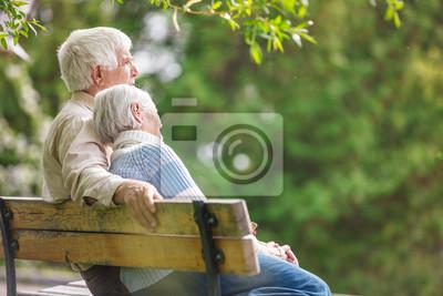 Plakat Osoby w podeszłym wieku para odpoczynku na ławce w parku