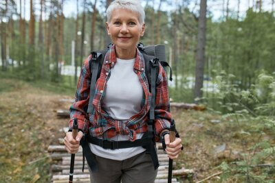 Plakat Outdoor activities, people and vacations concept. Attractive short haired middle aged woman in activewear hiking in forest using poles for nordic walking, doing aerobic workout, enjoying nature