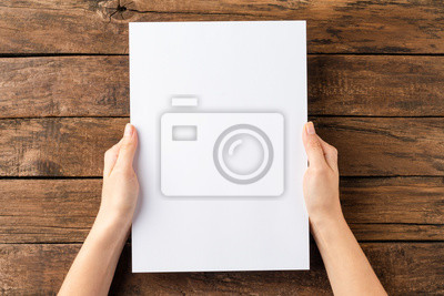 Plakat Overhead shot of woman's hands holding blank paper sheet on rustic wooden table. Close up