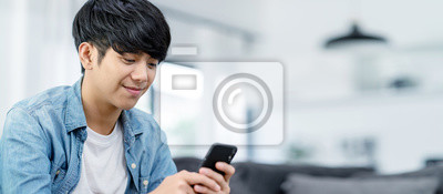 Plakat Panoramic or Banner of Happy asian teenager using smart phone and smiling on sofa living room at home. Asian man holding and using cellphone for searching data and social medie on internet.