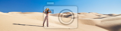 Plakat panoramic photo of lone woman standing in sand dunes with blue sky
