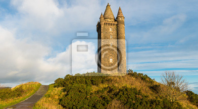 Plakat Panoramiczny widok ścieżki prowadzącej do starej wieży zamku na szczycie wzgórza pod błękitne niebo z białymi bufiastymi chmurami