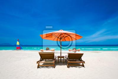 Para na tropikalnej plaży na leżakach pod czerwonym parasolem.