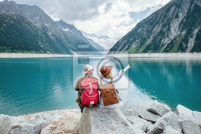 Plakat Para podróżników patrzy na górskie jezioro. Koncepcja podróży i aktywnego życia z zespołem. Przygoda i podróże w regionie górskim w Austrii. Podróż - obraz