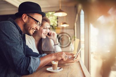 Plakat Para przy użyciu cyfrowego tabletu w kawiarni
