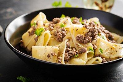 Pasta Calamarata with minced meat in black bowl. Italian cuisine.