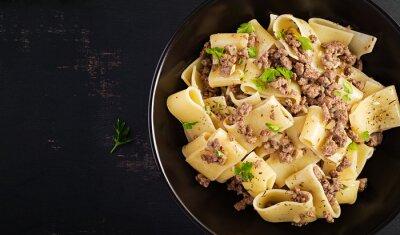 Pasta Calamarata with minced meat in black bowl. Italian cuisine. Top view, overhead