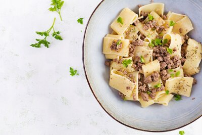 Pasta Calamarata with minced meat in blue bowl. Italian cuisine. Top view, overhead