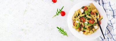 Pasta salad. Fusilli Pasta - Caprese salad with tomato, mozzarella and basil. Top view, banner, copy space
