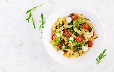 Pasta salad. Fusilli Pasta - Caprese salad with tomato, mozzarella and basil. Top view, flat lay, copy space