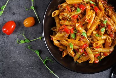 Penne pasta in tomato sauce with meat, tomatoes decorated with pea sprouts on a dark table. Top view