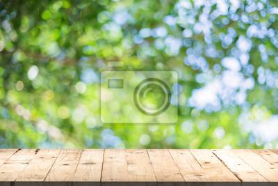 Plakat Perspektywa tabeli drewna i zielony liść bokeh niewyraźne na naturalne