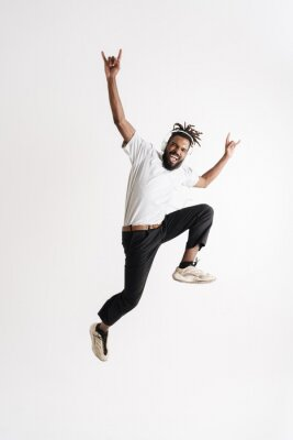 Plakat Photo of african american guy jumping while showing horn gesture