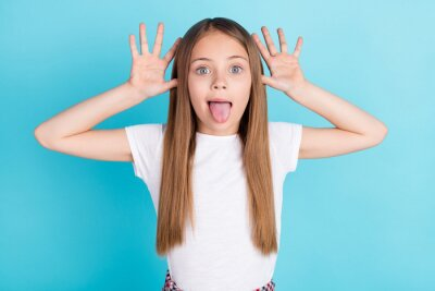 Plakat Photo of funky brown hair small girl hands head tongue out wear white t-shirt isolated on blue color background