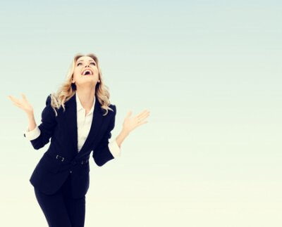 Plakat Photo of happy gesturing young cheerful businesswoman, with blank copyspace area for text or slogan
