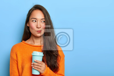 Plakat Photo of pensive brunette woman purses lips, looks thoughtfully aside, holds takeout coffee, makes decision in mind, plans her day, wears orange jumper, stands over blue wall. Asian girl with beverage