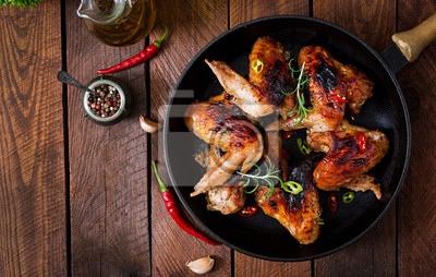 Pieczone skrzydełka kurczaka na patelni na drewnianym stole. Widok z góry