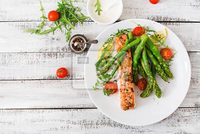 Pieczony łosoś przyozdobionym ze szparagami i pomidorami z ziołami. Widok z góry