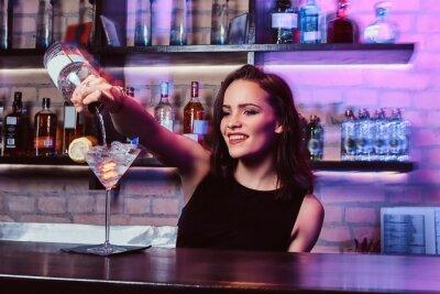 Plakat Piękna barmanka przygotowuje koktajl alkoholowy z wódką