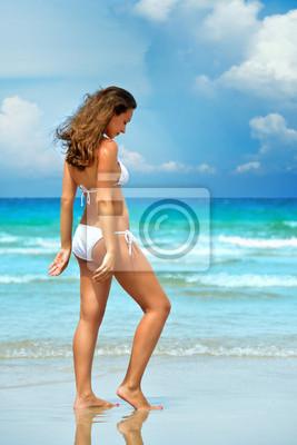 Piękna brunetka w białym bikini marzenia jednocześnie korzystając z s
