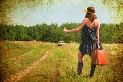 Plakat Piękna brunetka z walizką na wsi . Zdjęcia w