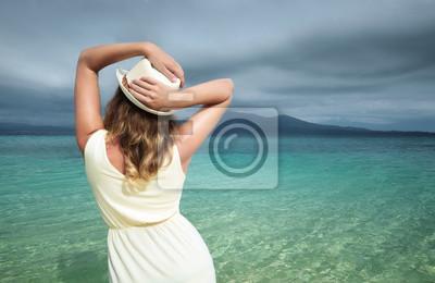 Piękna kobieta na sobie białą sukienkę na plaży na tle dramatycznego nieba.