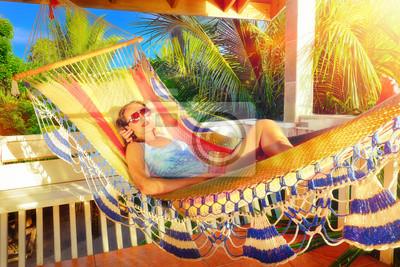 Plakat Piękna kobieta relaksuje się na hamaku w tropikalnym ogrodzie