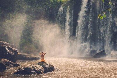 Plakat Piękna kobieta siedzi obok wodospadu ciesząc się słońcem, Phnom Koulen w Siem Reap, Kambodża
