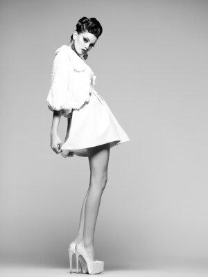 Plakat piękna kobieta z długimi nogami w białej sukni i wysokich obcasach