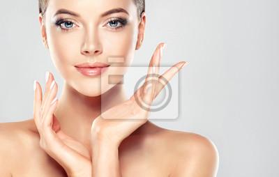Plakat Piękna młoda kobieta z czystego świeżego skóry dotykowym własnej twarzy. Zabieg na twarz . Kosmetyki, urody i spa.