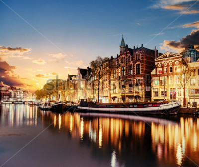 Plakat Piękna noc w Amsterdamie. Nocne oświetlenie statków i łodzi w pobliżu vody w kanały.