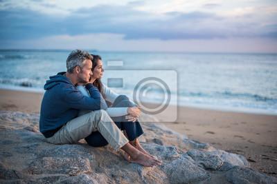 Plakat Piękna para siedzi na plaży oglądania zachodu słońca
