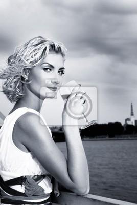 Plakat Piękne blond dziewczyna napojów szampana w pobliżurzeki