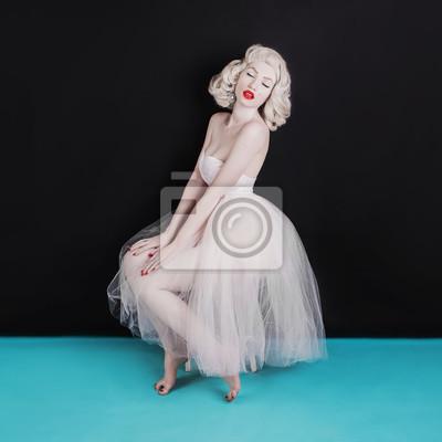 Plakat Pięknej sławnej blondynki seksowna kobieta z znamieniem na twarzy na czarnym tle. Młoda blada dziewczyna z blond włosami. Piękna seksowna kobieta w baletniczej spódniczce baletnicy z kolczykami na usz