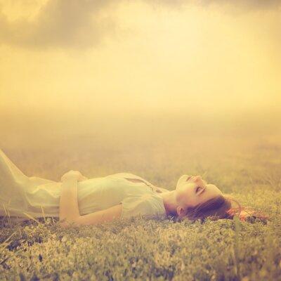 Plakat piękny, młody, dziewczyna marzy leżącego na magicznej łące wiosną