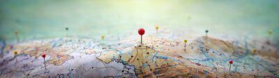 Plakat Pins on a geographic map curved like mountains. Pinning a location on a map with mountains. Adventure,  geography, mountaineering, hike and travel concept background.