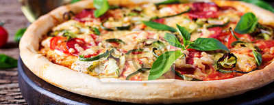 Pizza with chicken, salami, zucchini, tomatoes and herbs on vintage wooden background. Banner.  Italian cuisine