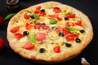 Pizza z pomidorami, mozzarellą, bazylią i oliwkami.