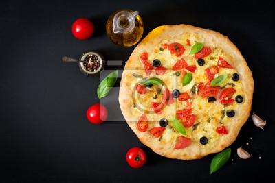 Pizza z pomidorami, mozzarellą, bazylią i oliwkami. Widok z góry
