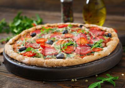 Pizza z salami, pomidorami, oliwkami i serem na cieście z mąką z całych pszenicy. Włoskie jedzenie.