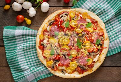Pizza z salami, pomidorem, serem i pieczarkami. Widok z góry