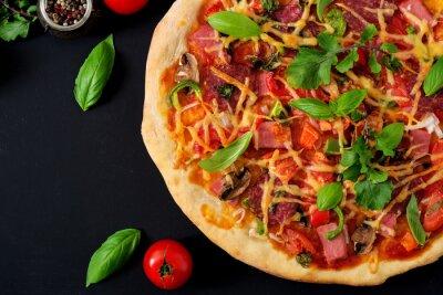 Pizza z salami, szynką, pomidorem, serem i pieczarkami. Widok z góry