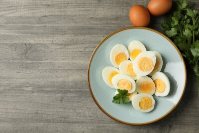 Plakat Plate with boiled eggs and parsley on gray background