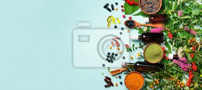 Plakat Podejście medycyny holistycznej. Zdrowe jedzenie, suplementy diety, zioła lecznicze i kwiaty. Kurkuma, suszona lawenda, sproszkowana spirulina w drewnianych miseczkach, świeże jagody, kapsułki z kwase