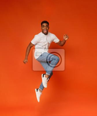 Plakat Podekscytowany afroamerykański mężczyzna skoki na pomarańczowym tle