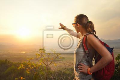 Podróżnik kobieta podróżująca z plecakiem korzystających z widoku zachodu słońca