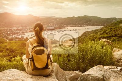 Podróżnik kobieta siedzi i patrzy na krawędzi klifu w zatoce morskiej