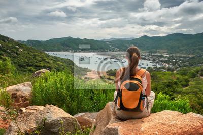Podróżnik kobieta siedzi i patrzy na krawędzi urwiska