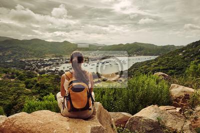 Podróżnik kobieta siedzi i patrzy na skraju gór