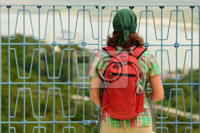 Podróżnik z plecak patrząc przez metalowe ogrodzenie na terenie zamkniętym do odwiedzenia